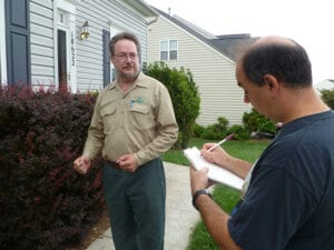 House exterior with Home Inspector talking with client